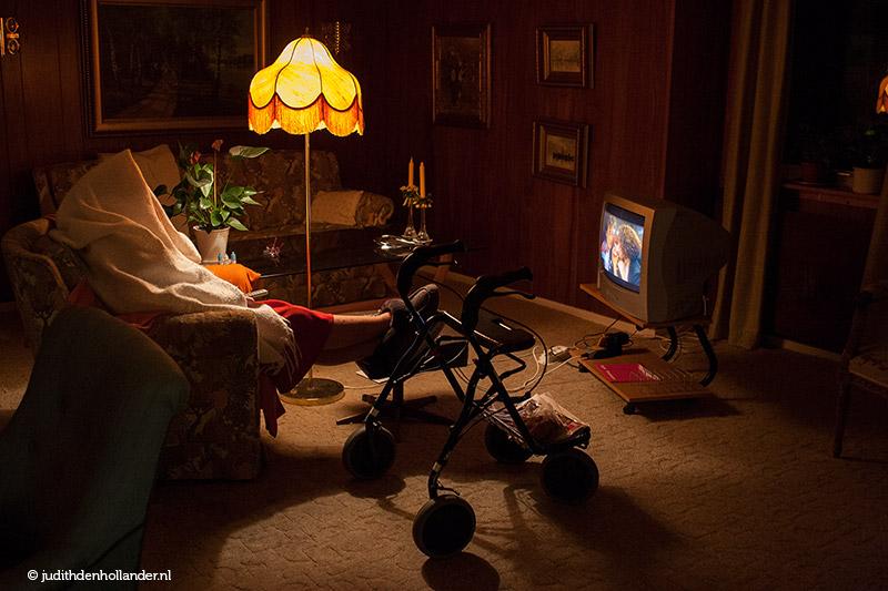 Environmental portrait of senior in font of TV