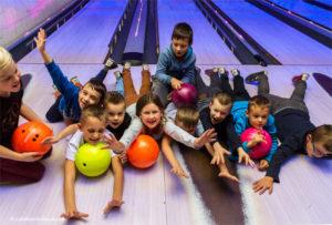 Kinderen hebben plezier op de bowlingbaan.