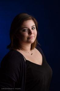 Mooi low key Studio portret van een jonge vrouw tegen een donderblauwe achtergrond | Fine art portretfotograaf Judith den Hollander.