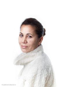 High key Studioportret | Jonge vrouw met wit 'bont' jasje tegen witte achtergrond | Fotografie Judith den Hollander.