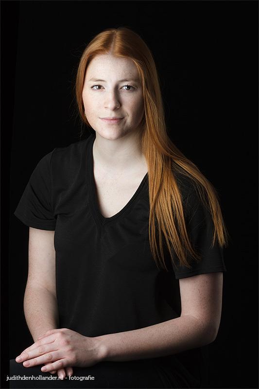 Klassiek Portret van een zittende jonge vrouw met lang rood haar © Judith den Hollander - fine art portretfotografie.