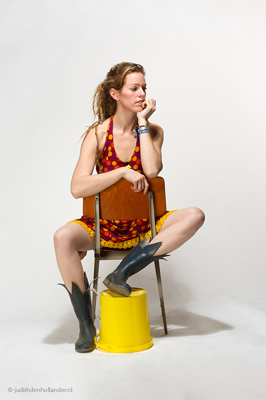 Beautiful young woman wearing a colourful dress and boots, sitting on a stool | Contemporary Portrait by Judith den Hollander