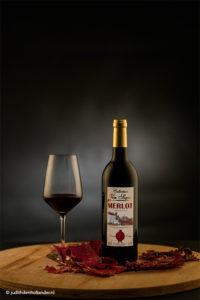 Rode wijnfles en wijnglas tegen een donkere achtergrond gefotografeerd - Fotostudio JDH Wittem.