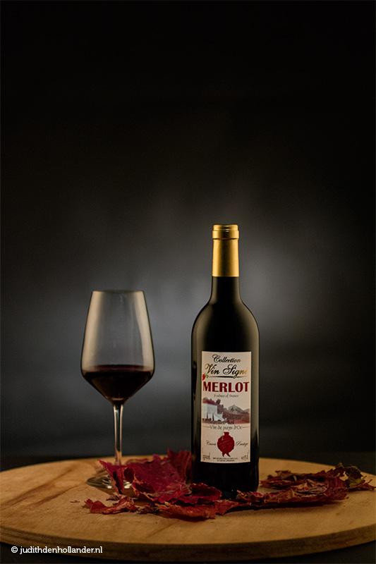 Wijnfles gestileerd | Rode wijnfles en wijnglas tegen een donkere achtergrond gefotografeerd - Fotostudio JDH Wittem.
