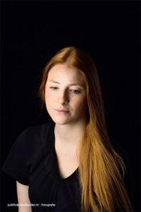 Fine Art Portret van een jonge vrouw met lang rood haar, donkere achtergrond | Klassieke portretfoto | Fotografie Judith den Hollander (Haarlem, Hasselt, Maastricht).