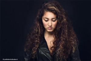 Studioportret van een jonge vrouw met lang krullend haar | Low key | Prachtige eenvoudig - Portretfotograaf Judith den Hollander