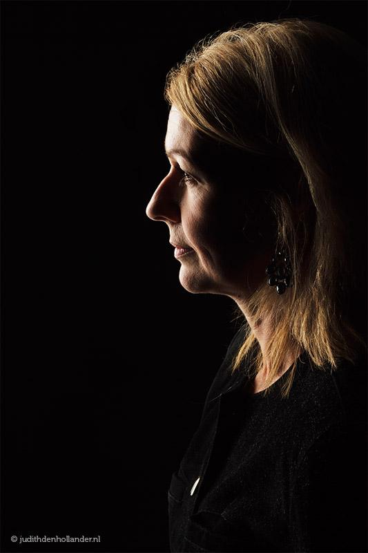 Low key portret, zwart op zwart, vrouw en profil | Portretfotografie Judith den Hollander.