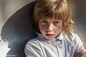 Mooi kinderportret   Daglicht foto van een blonde jongen met boeiende schaduw   Fotograaf Haarlem, Judith den Hollander.