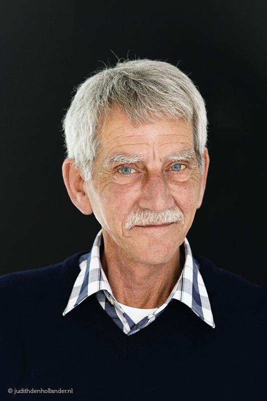 Profielfoto Haarlem   Daglicht portret van een seniore man tegen een zwarte achtergrond   Portretfotograaf Judith den Hollander, Haarlem.