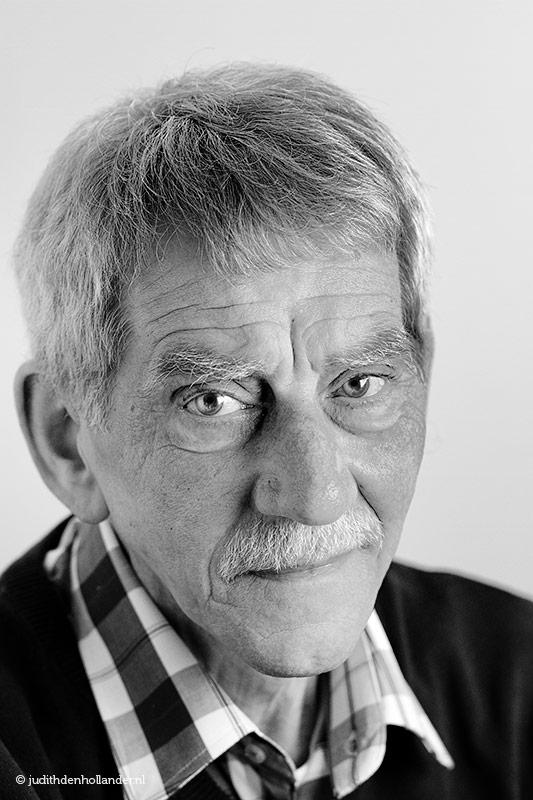 Daglicht portret seniore man   Close-up, Hoofd-schouders opname   Lichte achtergrond   Zwart-wit omzetting   Profielfotograaf Judith den Hollander, Haarlem.