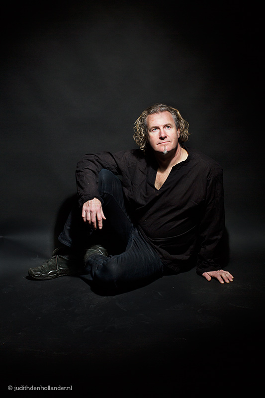 Portretfotografie | Portrait photography | Low key studio portrait. Man sitting on the floor pose | Photo © Judith den Hollander