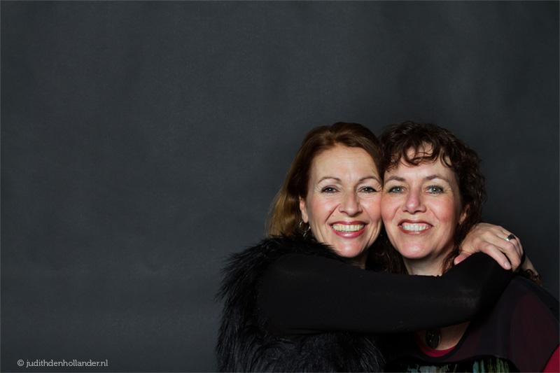 Dubbelportret van 2 lachende zusters voor een donkere achtergrond | Portretfotograaf Judith den Hollander (Hasselt, Maastricht, Haarlem).