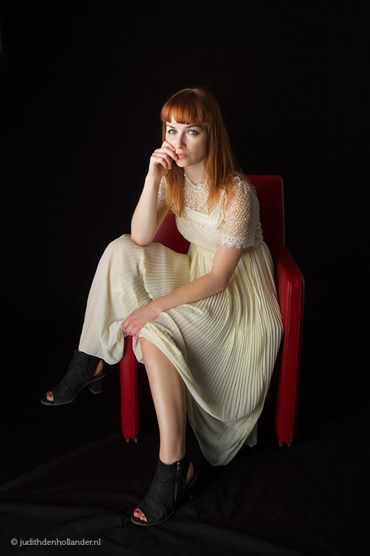 Fotokunst | Eigentijdse portretfoto | Mooi eigentijds portret van een jonge vrouw met rood haar in een rode stoel, zwarte achtergrond. Fotografie Judith den Hollander (Hasselt, Maastricht, Haarlem).
