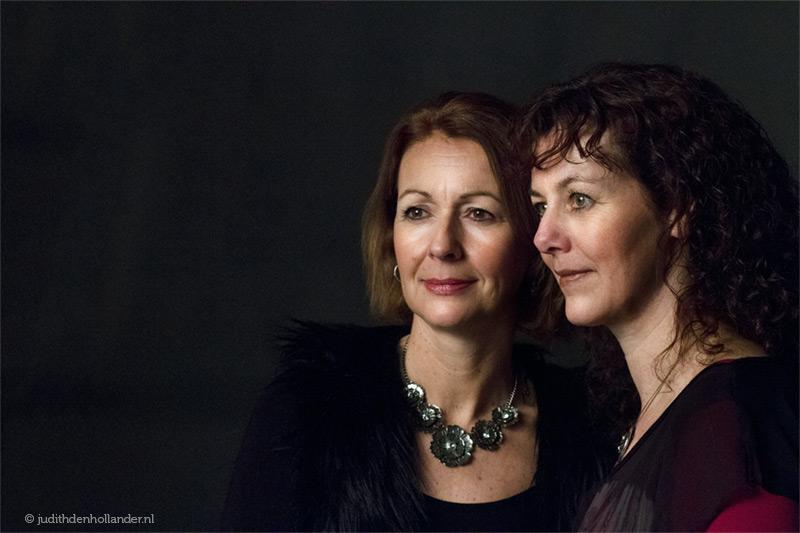 Mooi klassiek portret | Dubbelportret van zussen (zwarte achtergrond) | Fine art fotograaf Judith den Hollander (Maastricht, Haarlem).