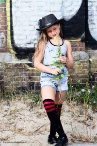 Tienermeisje ten voeten uit gefotografeerd tegen een graffiti muur   Ze is mooi gekleed, draagt een hoed en heeft een bloem in haar handen.   Portretfotograaf Judith den Hollander (Haarlem, Maastricht).