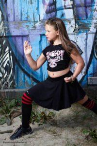 Tienermeisje in Kung-fu houding geportretteerd voor een graffitimuur.   Fotograaf Judith den Hollander (Haarlem, Maastricht).
