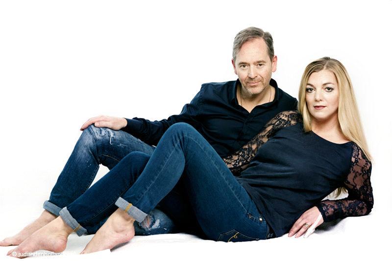 Eigentijds dubbelportret van man en vrouw liggend op de vloer tegen een lichte achtergrond | Fine art fotografie Judith den Hollander (Haarlem, Maastricht).