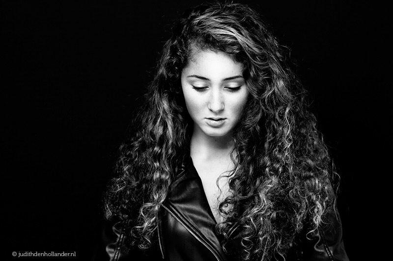 Fine art portret van een jonge vrouw met lang krullend haar tegen een donkere achtergrond | Sereen beeld | Studio JDH, Haarlem en Maastricht.