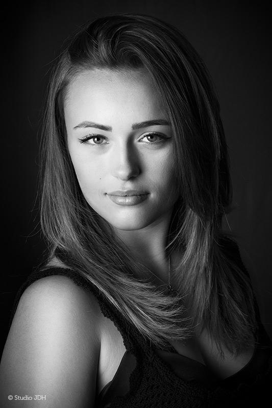 Beauty portretfotografie, nu ook in Haarlem | Fine art fotograaf werkt sinds januari de regio Haarlem | Fine art portretfotograaf J. den Hollander fotografeerde hier een jonge vrouw met lang haar tegen een donkere achtergrond | Foto omgezet naar Zwart-Wit.