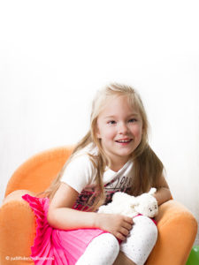 In-Home photoshoot | Young girl with a toy in an orange chair against a light background | In-huis fotoshoot Hoofddorp | Fotografie J. den Hollander.