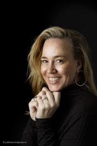 Portet van een lachende vrouw met een zwarte trui tegen een zwarte achtergrond. Fotograaf Judith den Hollander, Haarlem.