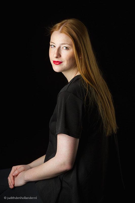 Klassiek portret van een jonge vrouw met lang rood haar tegen een donkere achtergrond | Fine art fotografie | Studio JDH, J. den Hollander.