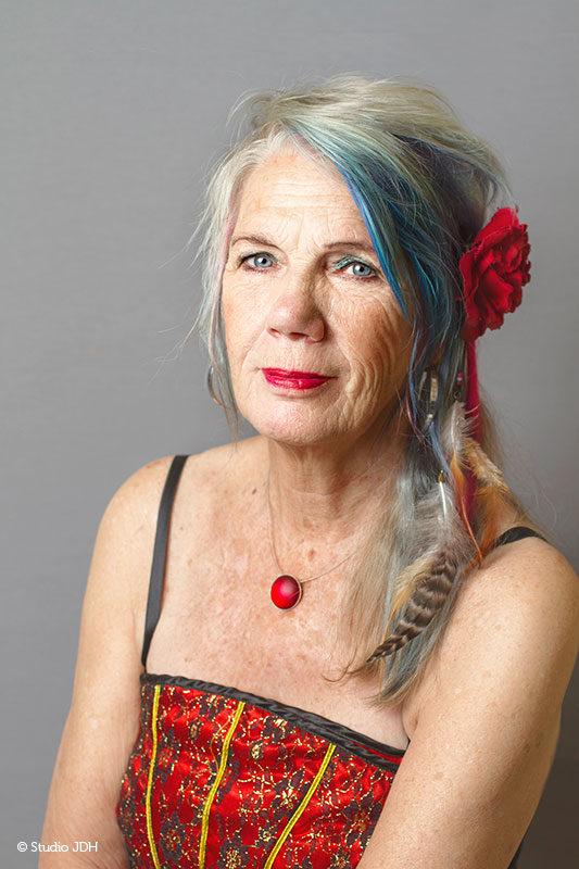 Portret met kleur en karakter | Portret van een vrouw tegen een grijze achtergrond | fine art fotografie Studio JDH Haarlem.