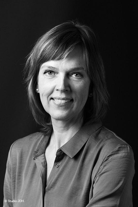 Klassiek Portret in zwart-wit | Vrouw geportretteerd tegen een donkere achtergrond | In-home fotosessie | Fotograaf J. den Hollander, Haarlem.