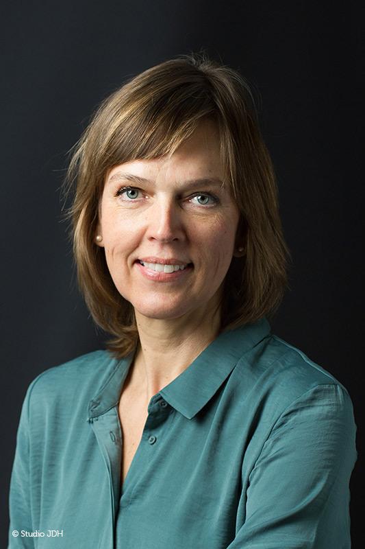 Zakelijk-Klassiek | Klassiek portret | Vrouw met een groene blouse geportretteerd tegen een donkere achtergrond | Fotograaf J. den Hollander, Studio JDH, Haarlem en Maastricht.