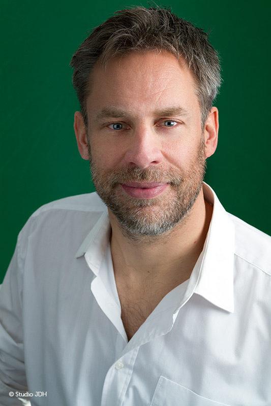 Zakelijke portretfoto met kleur | Man met wit overhemd geportretteerd tegen een groene achtergrond | Fotograaf J. den Hollander, Haarlem en Maastricht.
