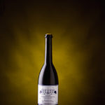 Professionele Wijnflessen Fotografie | Sfeerbeeld wijnfles met druiven | Productfoto met impact | Vakfotografie WijndomeinFotografen Limburg | Belgische Chardonnay.