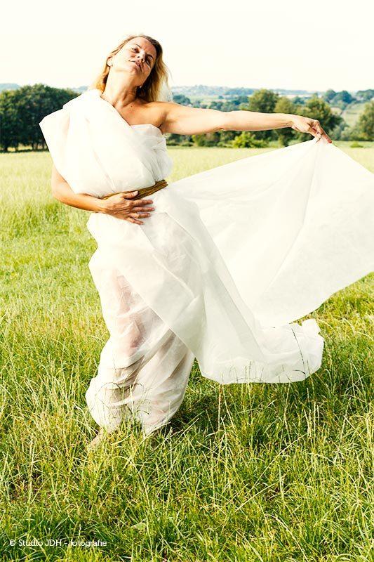 Fotoshoot in de natuur, op locatie | Vrouw in een groen veld met een lange witte zelfgemaakte jurk | Expressief.