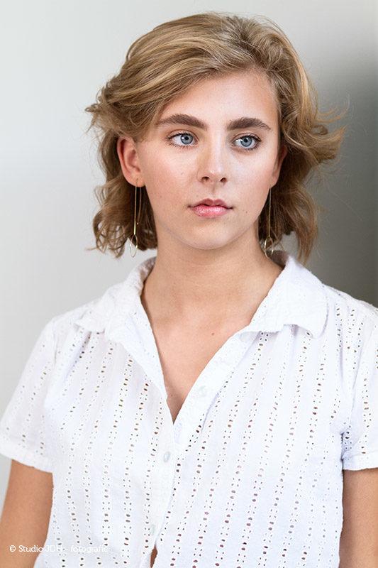 Castingportret van een jonge vrouw tegen een neutrale achtergrond, neutrale pose | Studio JDH, fotograaf J. den Hollander, Haarlem.