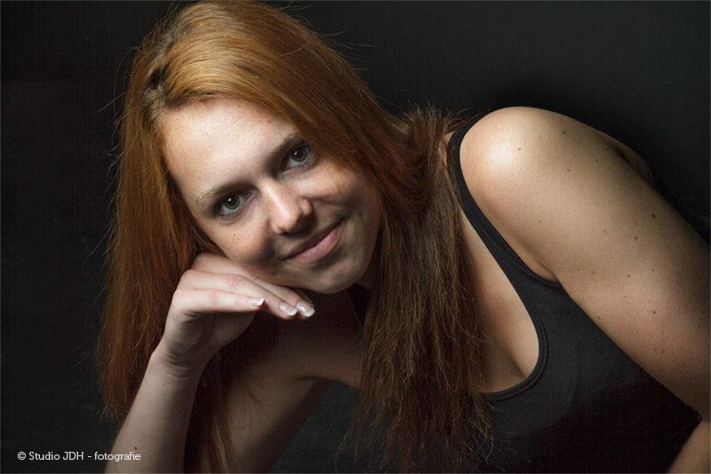 Portret van een vrouw met lang rood haar liggend op de grond. Ze ondersteunt haar hoofd met rechterarm. Zwart-op-zwart.