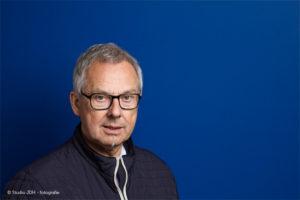 (Zakelijke) Portretfoto met kleur | Man met bril voor een blauwe achtergrond | Portretfotograaf J. den Hollander, werkzaam in Maastricht en Haarlem.
