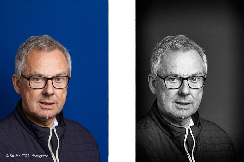 Zakelijke portretfoto van een man met bril tegen een blauwe achtergrond, in kleur en zwart-wit. Zakelijk portret, gemaakt in Maastricht.