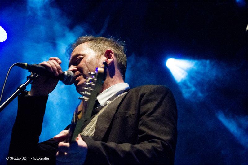 De zanger van The BieT, een rock cover band in Haarlem, in actie in Patronaat. Personal Branding Portretfoto van een man tijdens een muziekoptreden met blauw gekleurd licht en rookeffect.