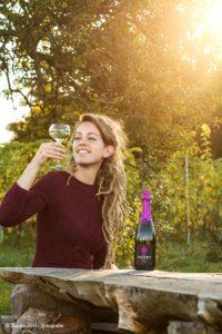 Lifestyle Reclamefoto van een jonge vrouw aan een houten tafel in de wijngaard, genietend van een glas  Nederlandse wijn. Zakelijk portret, gemaakt door fotograaf J. den Hollander.