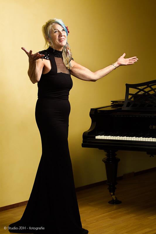 Portret van een Pianiste bij haar vleugel voor een kleurde (geel) achtergrond. Personal Branding Portret. Fotografie Judith den Hollander, Haarlem.