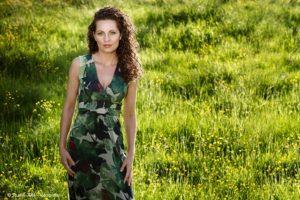 Fashion Flair Fotoshoot op een mooie groene locatie. Jonge vrouw draagt een lange groene jurk en staat in een fris groen veld met veldbloemen. Fotograaf Judith den Hollander, Maastricht en Haarlem.