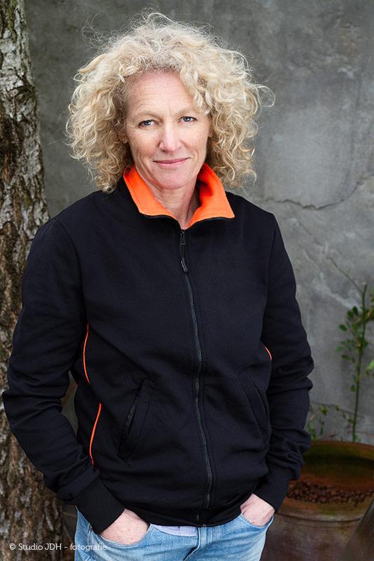 Daglicht portret van een sportieve vrouw, gemaakt in de tuin. Portretfotograaf J. den Hollander, Haarlem.