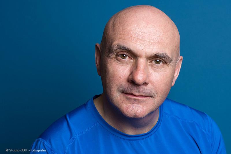 Headshot | Een sportieve hoofd-schouders portretfoto van een man met een blauw sportshirt gefotografeerd tegen een blauwe achtergrond. Portretfotograaf J. den Hollander, Haarlem.