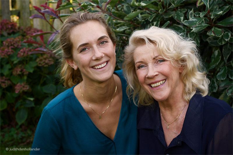 Dubbelportret. Daglicht opname van dochter en moeder in de tuin. Omgevingsportret.