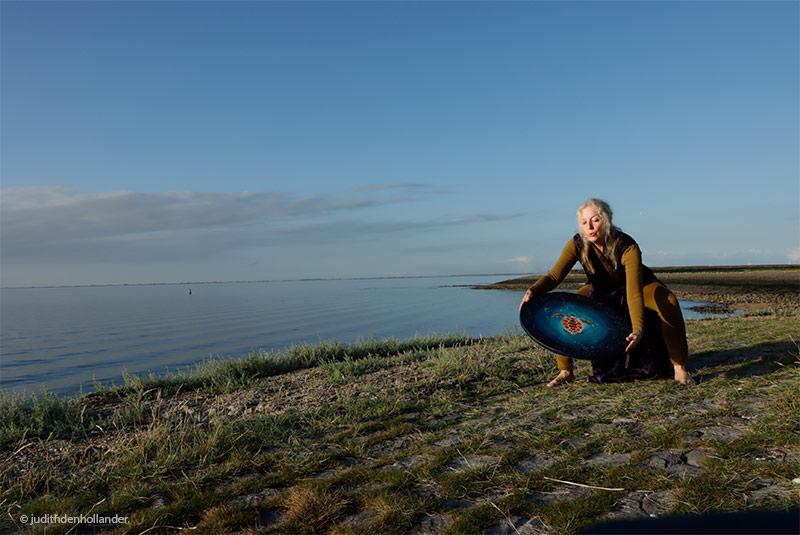 Pia Brand met haar oceaandrum in Zeeland. Portret van een artieste, gemaakt tijdens het gouden fotografen uurtje. Fotografie Judith den Hollander.