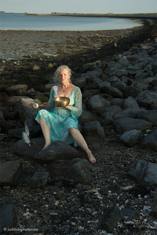 One of the photos from 3 shoots we did together in Zeeland, NL.  A woman dressed in a blue aquamarine dress sitting at darks rocks near the water, looking like a fairy tale mermaid, washed ashore with a purpose. She has a sound healing bowl in her hand. Photo by fine art photographer Judith den Hollander.
