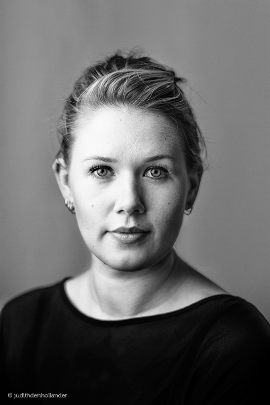 Klassiek portret van een jonge vrouw in zwart-wit. Middengrijze achtergrond. Fotografie J. den Hollander.